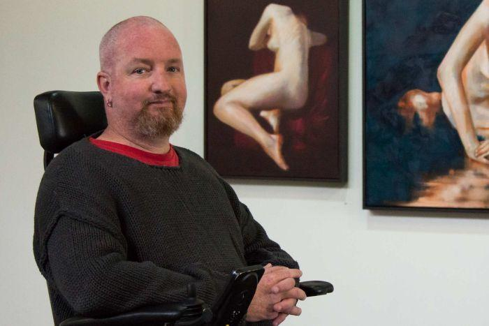 Andrew Grant sits in front of his paintings and is smiling