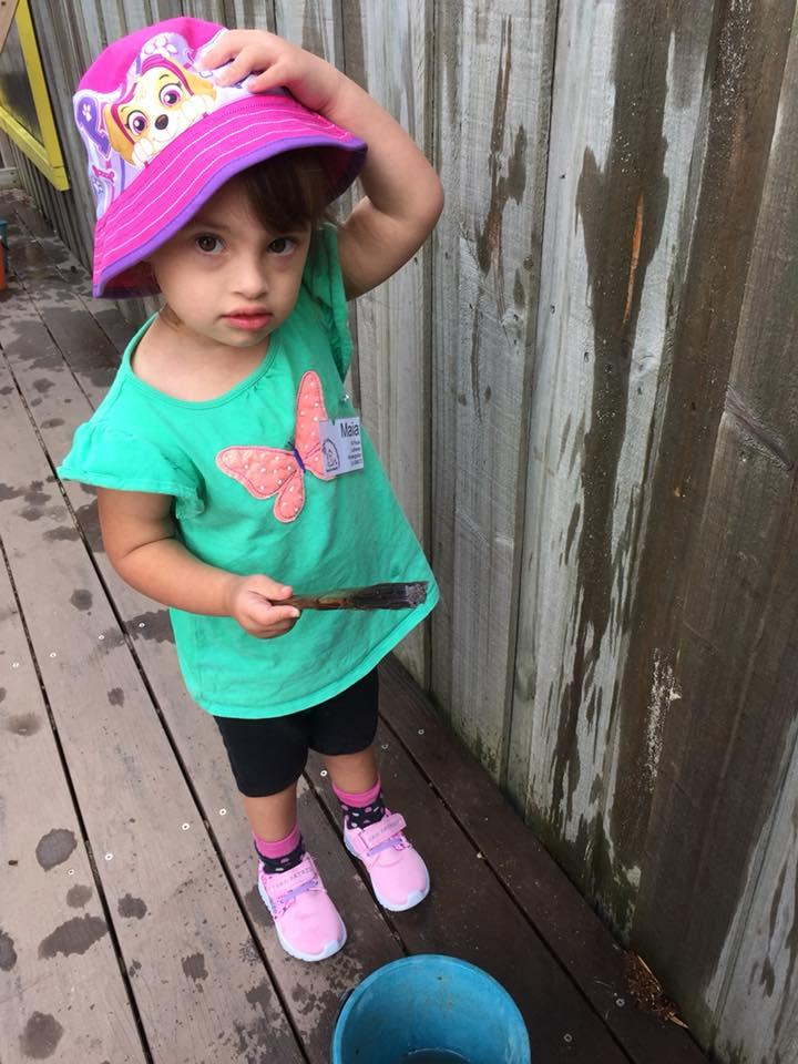 Maia wearing a pink hat at kindy