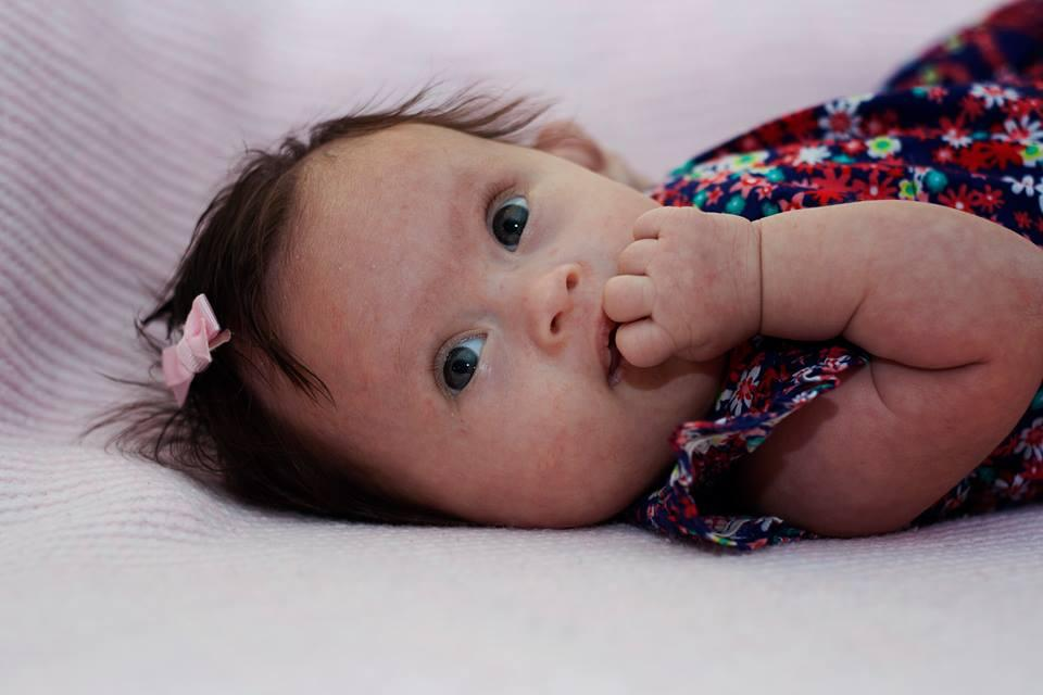 Close up of Maia lying down with her fingers in her mouth
