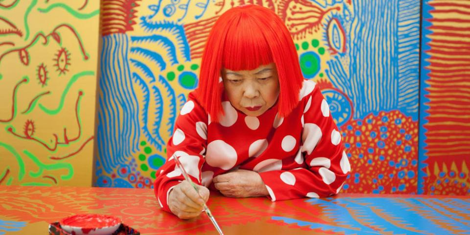 Yayoi deeply focuses on painting, and she has bright red hair and a red polka dot shirt