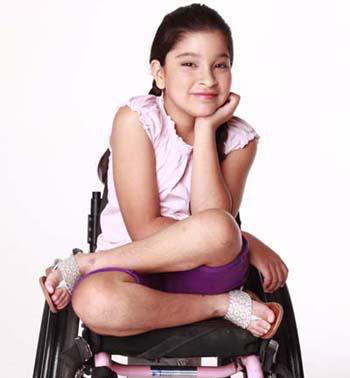 lourdes sits cross legged in her wheelchair and smiles with her face resting in one hand