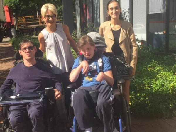 Nicole and Kate from MyCareSpace standing behind 2 people in wheelchairs