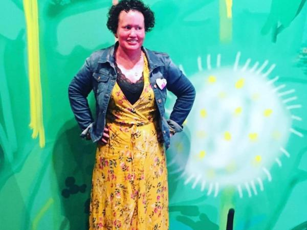 Carly posing, wearing a yellow dress and jean jacket