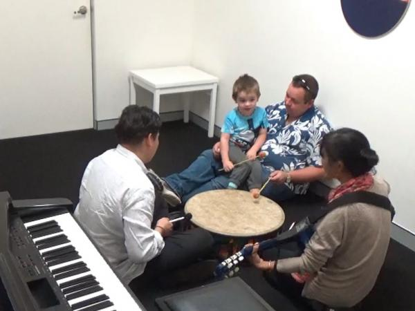 Darcy sitting on his fathers lap in the music lab