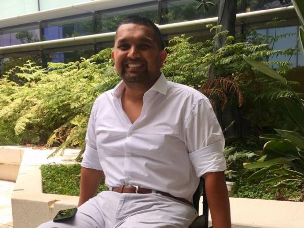 Dinesh Palipana sitting outside and smiling proudly