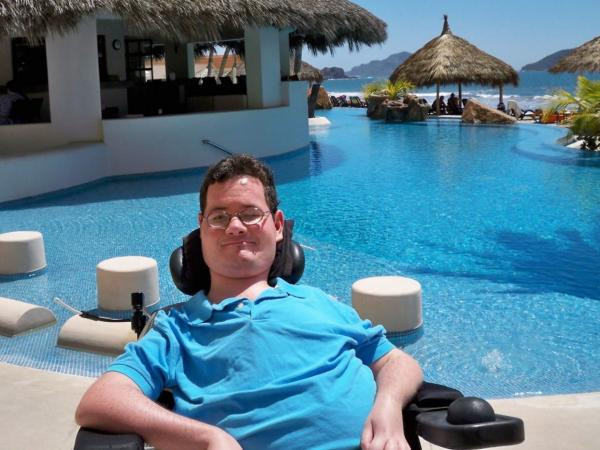 Jon Morrow sits outside smiling in a tropical villa in front of a pool