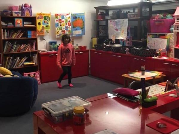Chantae standing in her home school classroom surrounded by games and books
