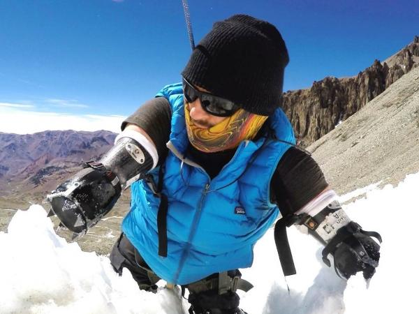 Kyle Maynard climbing up a snow covered mountain