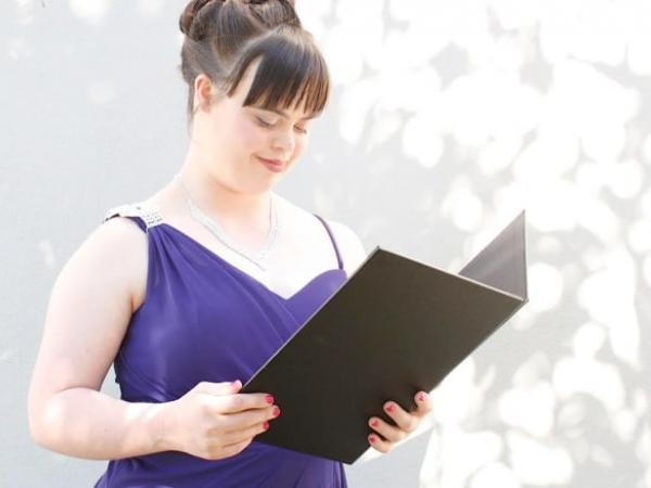 Olivia stands in a purple formal dress, speaking from a folder