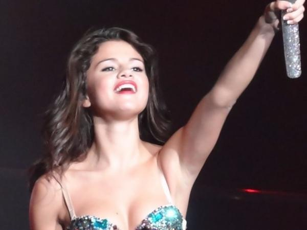 Selena Gomez standing on stage and smiling while holding her microphone out to audience