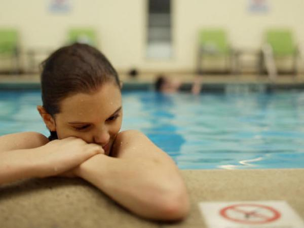 Somber woman rests head at edge of pool