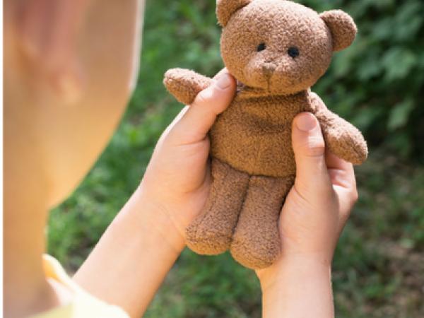 child holding brown teddy bear