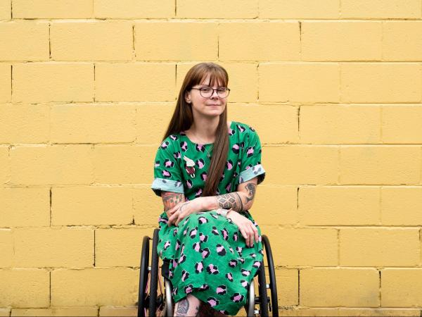 Nicole Lee in front of a yellow wall