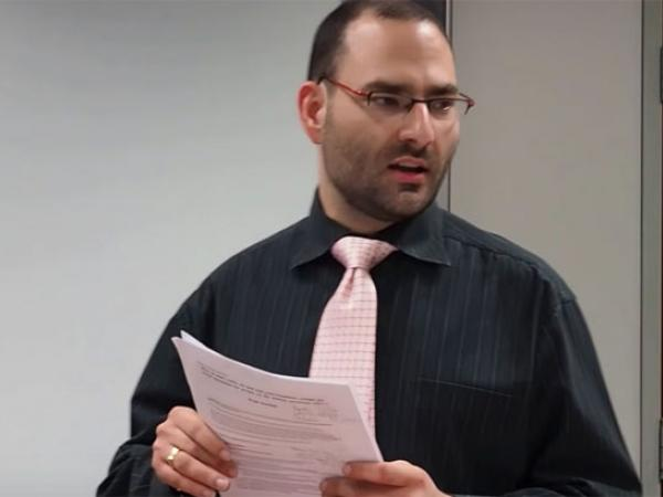 Paul standing speaking holding his notes and wearing a pink tie