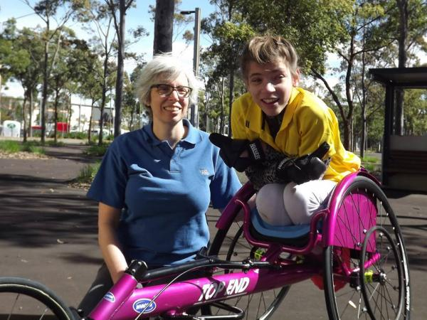 sarah in her multisport wheel chair with her trainer